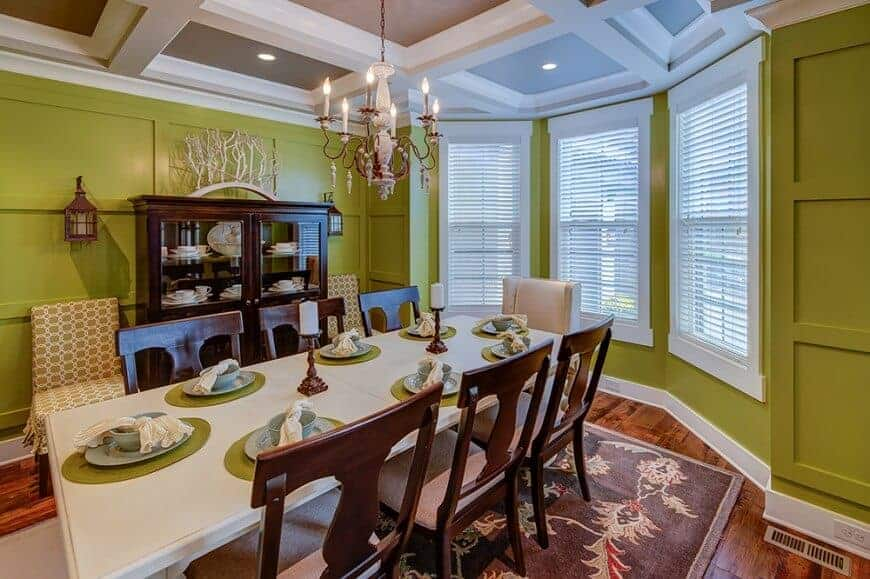 Green dining room with hardwood flooring and coffered ceiling mounted with recessed lights and a candle chandelier. It has a dining set for eight and a dark wood display cabinet flanked by sconces and skirted chairs.