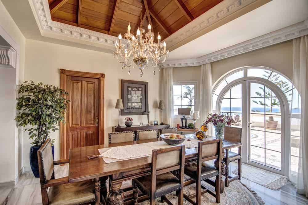 Bright dining room furnished with a wooden dining set and a console table that's topped with lampshades. It has a gorgeous chandelier and an arched French door leading out to the balcony with an expansive view.