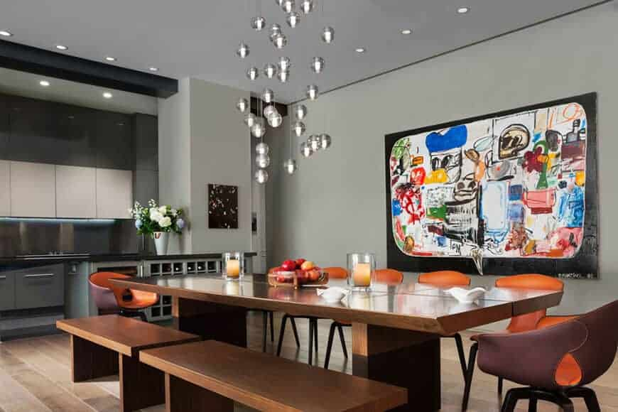 Gorgeous dining room decorated with colorful wall art and glass globe pendants that hung over the rectangular dining table paired with wooden benches and stylish leather chairs.