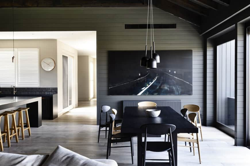 A black canvas mounted on the gray shiplap wall complements with the pendant lights and rectangular dining table surrounded with stylish seats over wood plank flooring.