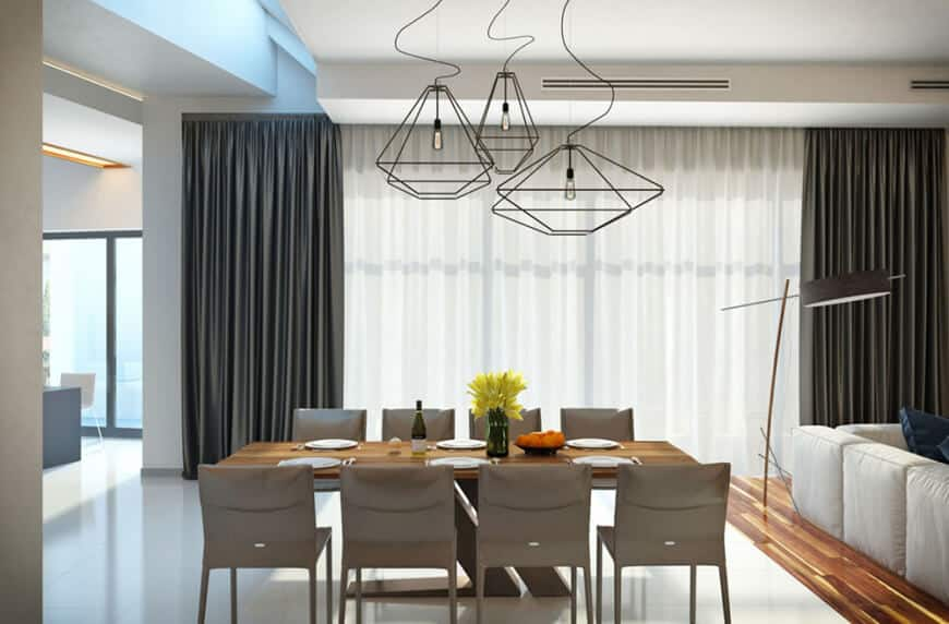 A sleek dining area with tiled flooring and full height glazing covered with gray draperies and white sheer curtains. It has taupe chairs and a wooden dining table lighted by geometric pendant lights.