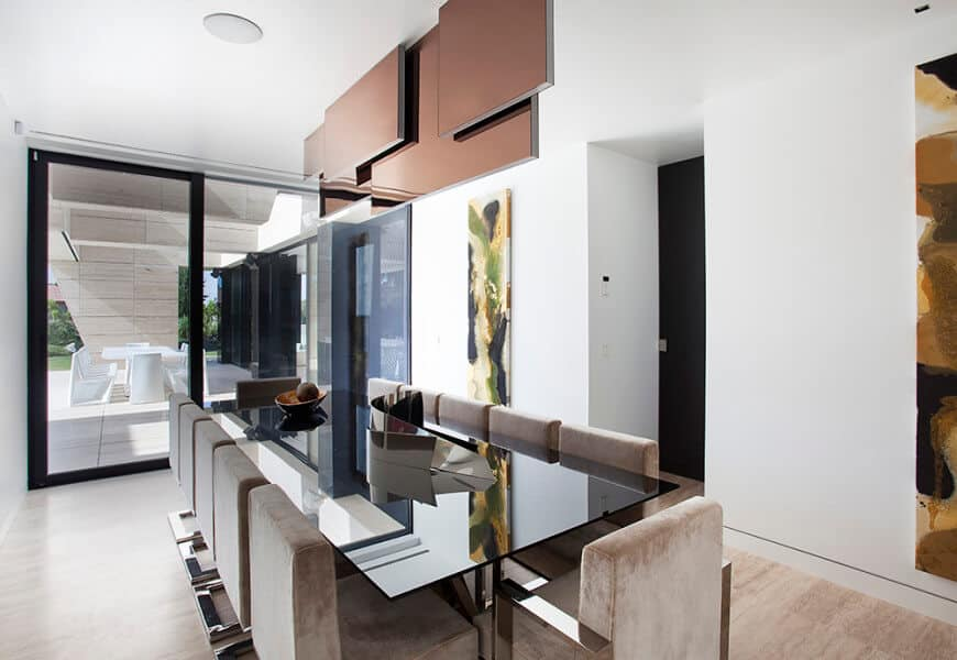 Abstract wall arts add a gorgeous accent in this modern dining room with brown velvet chairs and a rectangular glass dining table topped with a black bowl.