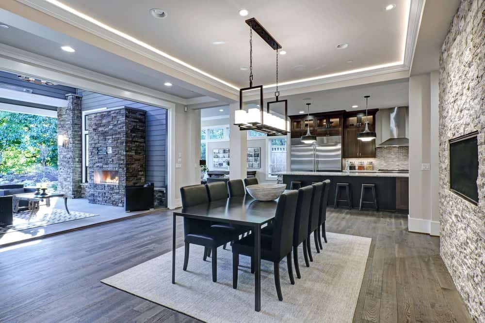 An open dining area offers black dining set on a beige rug along with a modern fireplace fitted on the stone accent wall. It has natural wood plank flooring and a tray ceiling with a hanging linear chandelier.