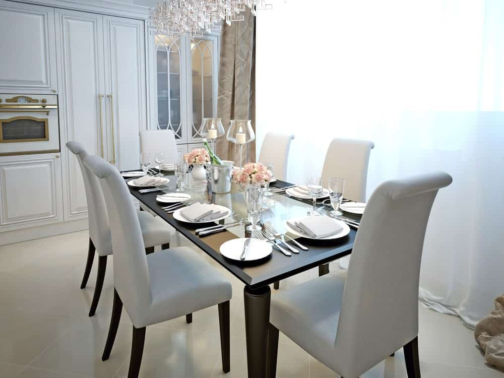 Elegant dining room with a sleek black dining table contrasted by white high back chairs on tiled flooring. It includes a gorgeous chandelier along with built-in cabinets and oven insert accented by brass hardware.