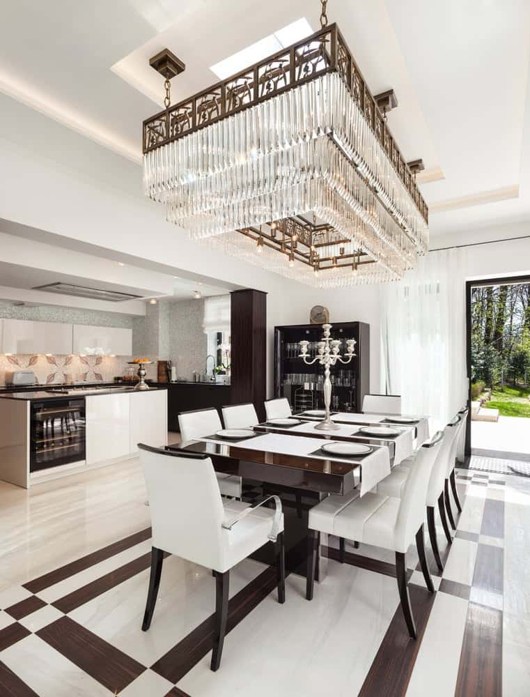 A stunning crystal chandelier illuminates this dining area boasting white upholstered chairs and a dark wood dining table with a glossy finish.