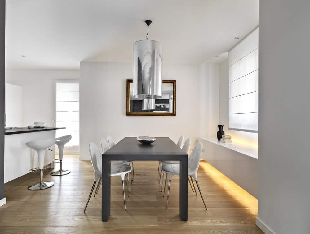 A cylindrical chrome pendant hangs over the gray dining table topped with a decorative bowl and accompanied by white chairs and a wooden framed mirror mounted on the white wall.