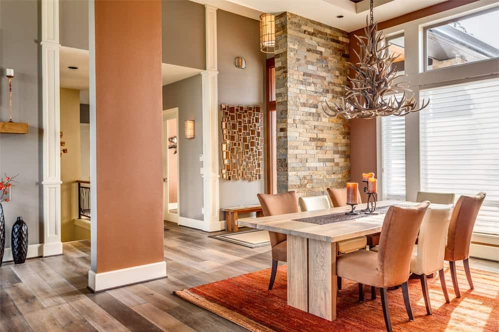 A stone brick wall adds texture in this dining room illuminated by an antler chandelier that hung over the wooden dining table and upholstered chairs on a coral area rug.