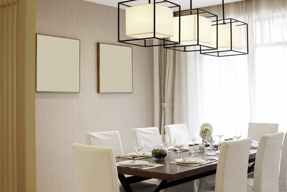 Neutral dining room decorated with a pair of canvases mounted on the beige wall. It has cube pendant lights and a dark wood dining table surrounded by white skirted chairs.
