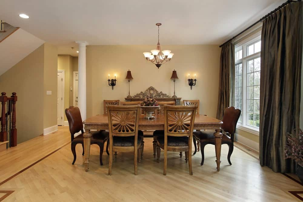 Beige dining room with hardwood flooring and white framed windows dressed in classy draperies. It is illuminated by candle sconces and a chandelier that hung over the wooden dining set.