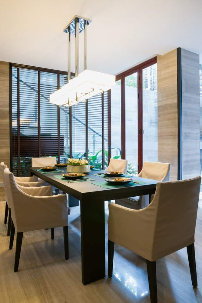 This dining room features beige upholstered chairs and a black dining table lighted by a linear chandelier along with natural light that flows in through the full height glazing.