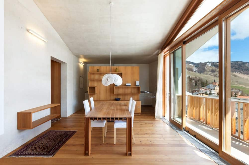 Ample natural light flows in through the glass sliders that open to the balcony with an amazing mountain view. There's a wooden dining set in the middle that blends in with the wood plank flooring and shelves.