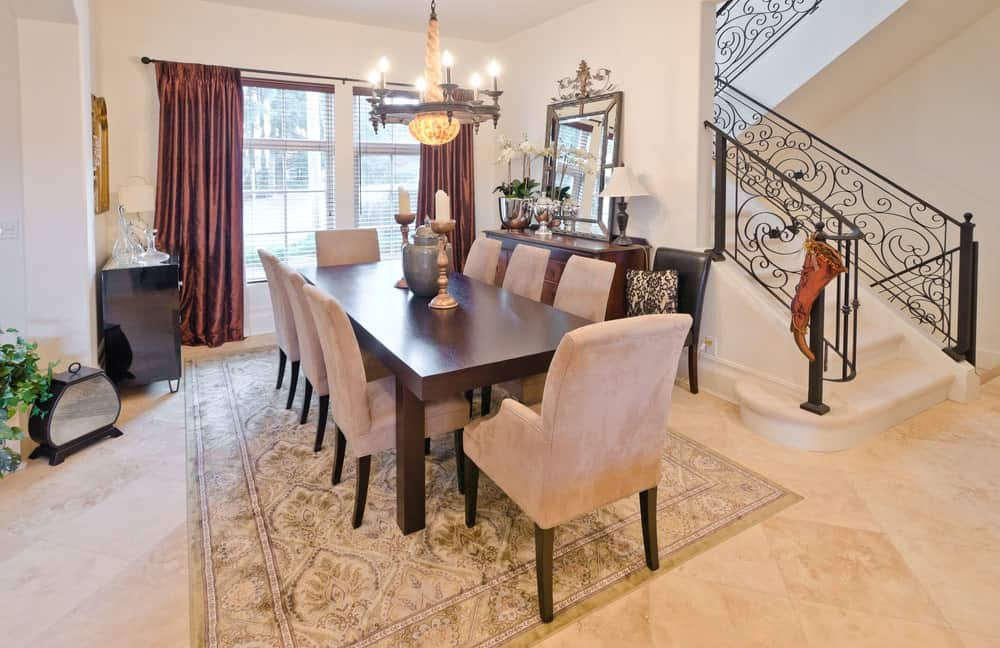 A dining area next to the ornate staircase with classy dining set and a wooden buffet table topped with lampshade and a gorgeous mirror. It includes a marvelous chandelier and a patterned area rug that lays on the marble flooring.