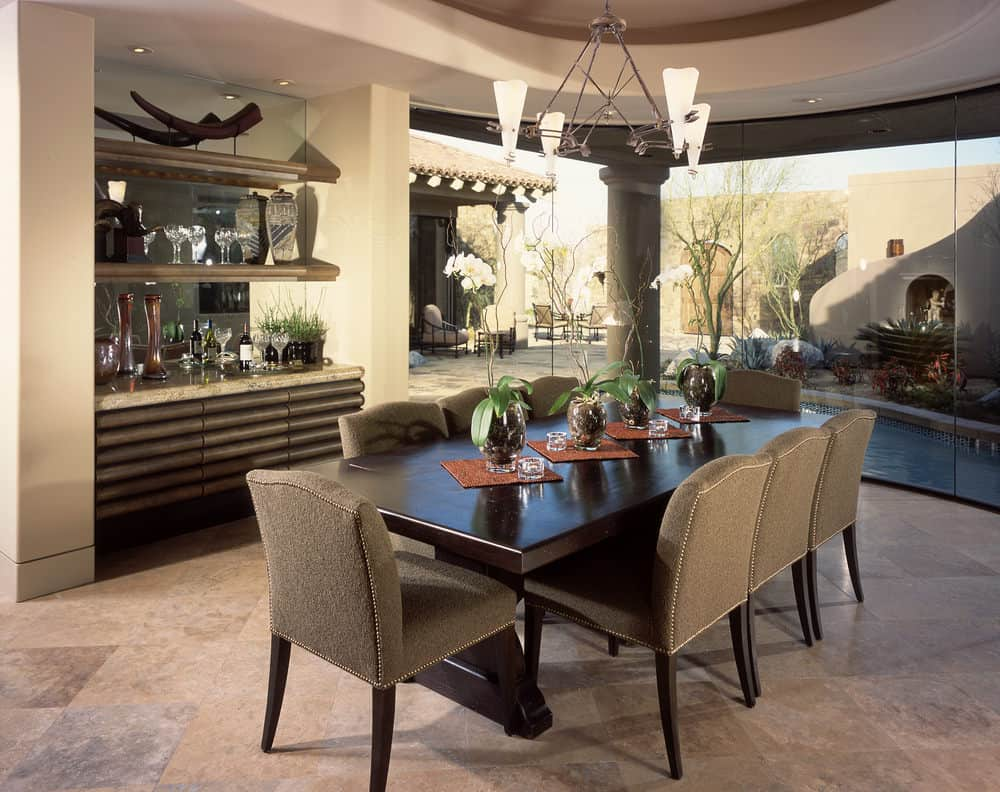 This dining area features gray upholstered chairs and a dark wood dining table lighted by a chandelier that hung from the tray ceiling.