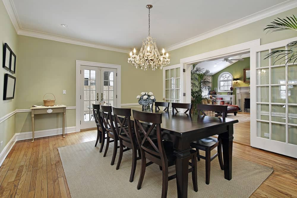 Fresh dining room with black framed wall arts and a mini table next to the French door. It includes a crystal chandelier and a dark wood dining set that sits on a textured rug.