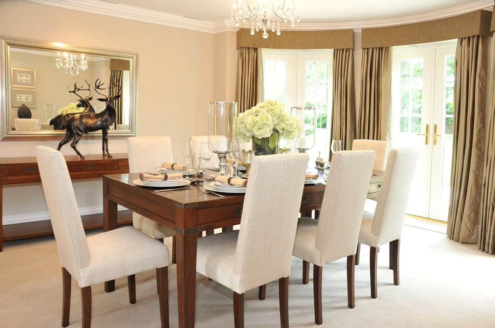 A stag decor sits on a wooden console table in this dining room offering a rectangular dining table and upholstered chairs matching with the beige area rug.
