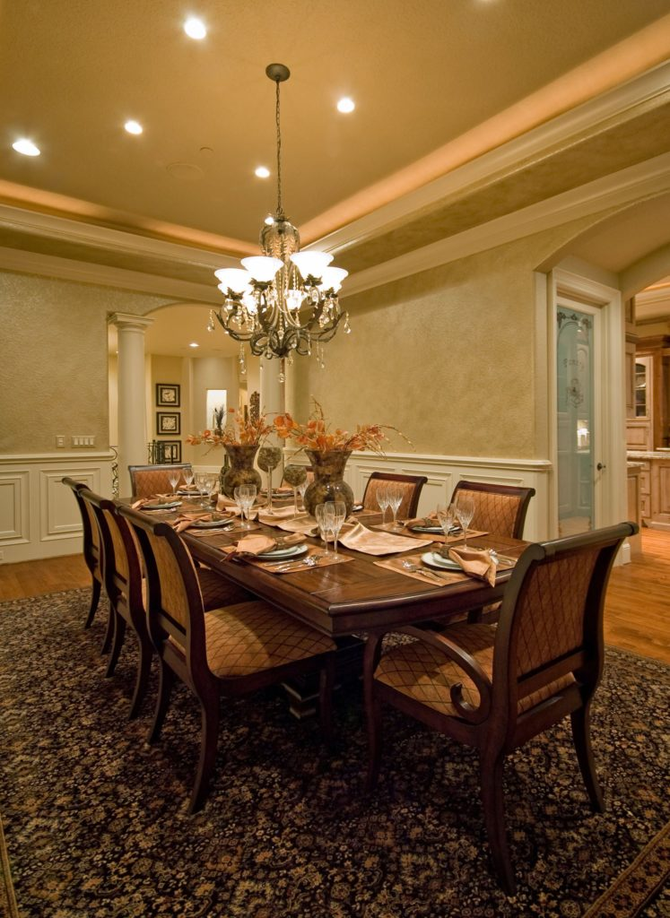 This dining room boasts a rectangular dining table and diamond patterned chairs over a black floral rug. It is illuminated by a fancy chandelier and recessed lights mounted on the tray ceiling.