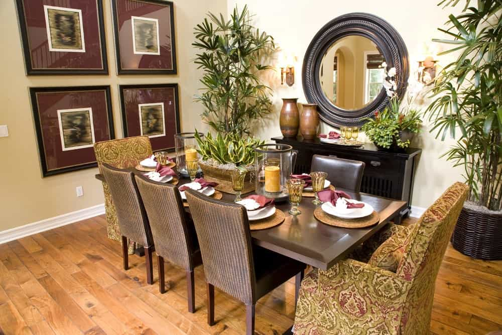 Tropical dining room decorated with gallery frames and a round mirror that hung above the black console table. It includes a rectangular dining table surrounded by leather and skirted chairs over wood plank flooring.