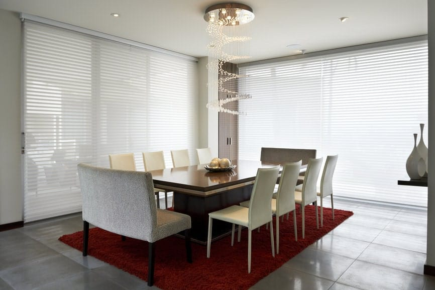 A cascading crystal chandelier illuminates this dining room offering a smooth dining table paired with white chairs and gray benches on a red shaggy rug.