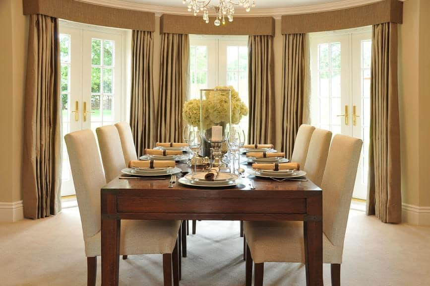 Beige upholstered chairs sit at a wooden rectangular table in this warm dining room with carpet flooring and French doors covered in taupe draperies.