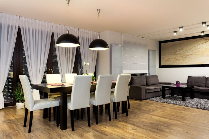 A spacious dining area with large black dome pendants and a smooth rectangular dining table surrounded with white leather chairs over the natural hardwood flooring.