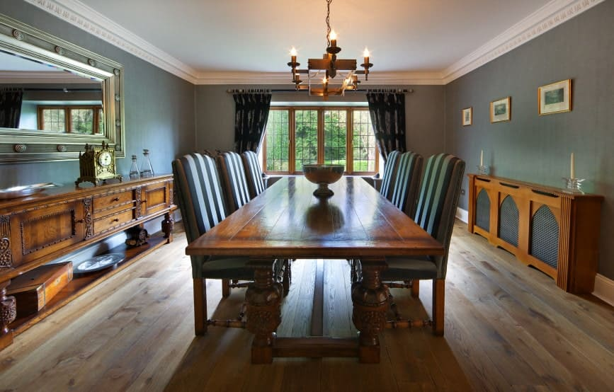 Gray dining room boasts a classic dining set situated in between the wooden console tables highlighted by framed wall arts and a rectangular mirror.
