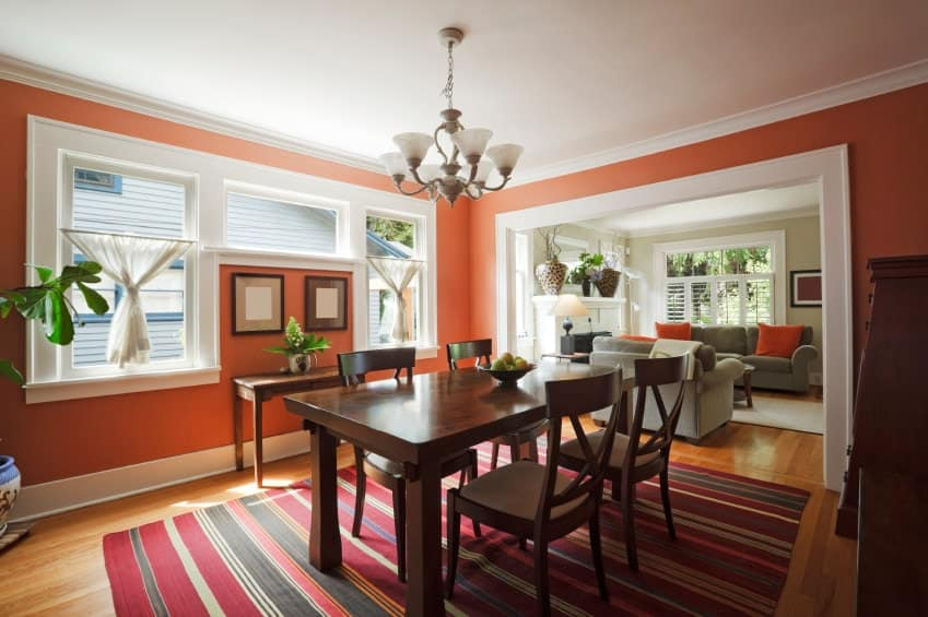 Red striped rug adds a striking accent in this coral dining room with a wooden dining set and a matching console table accented with black framed wall arts.