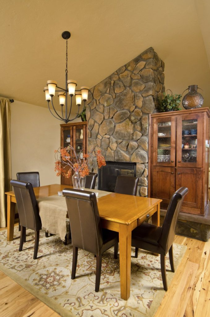 This dining room features a cozy dining set and display cabinets with a fireplace in the middle fixed on the stone pillar. It includes a wrought iron chandelier and a printed area rug that lays on the natural hardwood flooring.