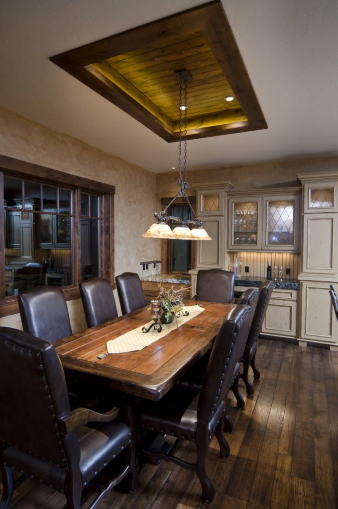 Cozy dining room with black leather chairs and a rectangular dining table illuminated by dome pendant lights that hung from the tray ceiling clad in wood planks.