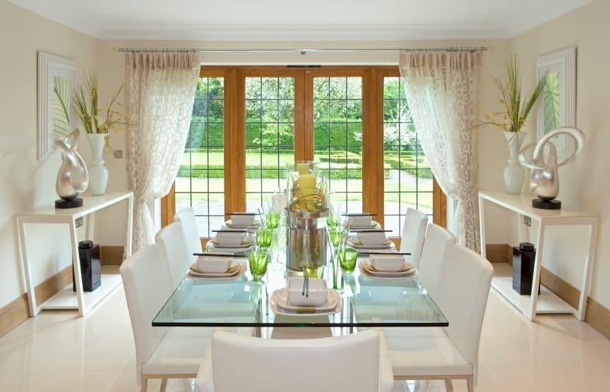 Airy dining room showcases a glass top dining table and white chairs that complement the console table topped with vases and chrome decors. It has tiled flooring and wooden framed windows overlooking the lush greenery.