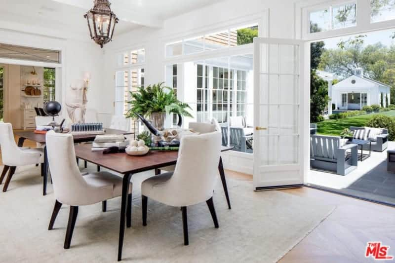 Bright dining area with chevron wood flooring and white framed doors leading out to the open patio. It includes upholstered chairs and a rectangular dining table lighted by a vintage pendant.