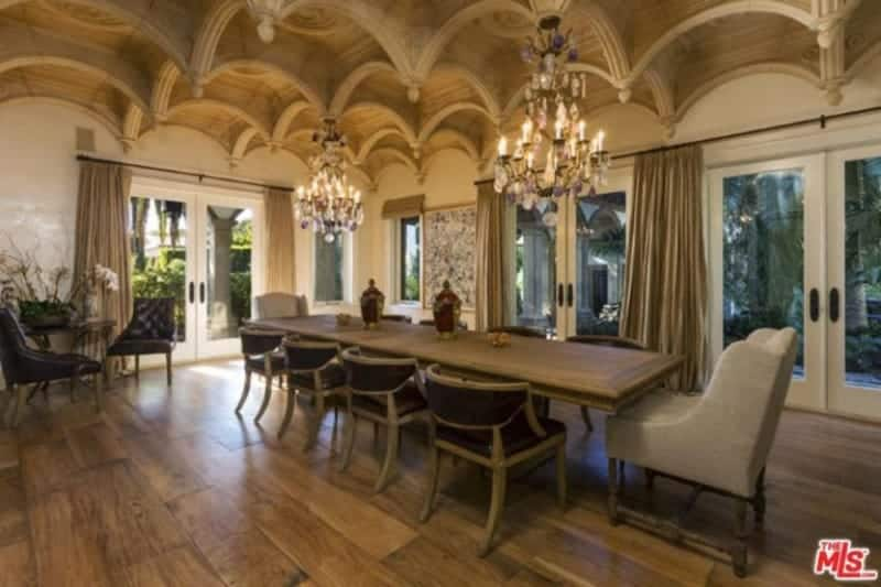 Magnificent dining room illuminated by a pair of candle chandelier that hung from the stylish ceiling. It has a long rectangular dining table paired with round back and gray wingback chairs.