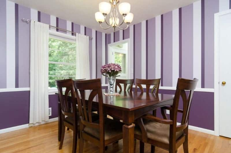 Clad in purple striped wallpaper, this dining room features a chrome chandelier and a dark wood rectangular table surrounded with beige cushioned chairs.