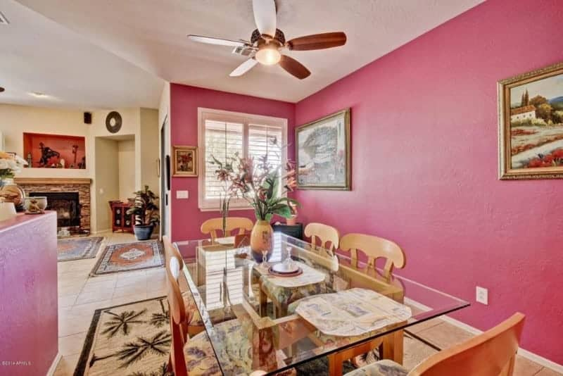 A charming dining area decorated with gold framed art pieces mounted on the pink wall. It has a glass top dining table and wooden chairs that sit on a tropical area rug.