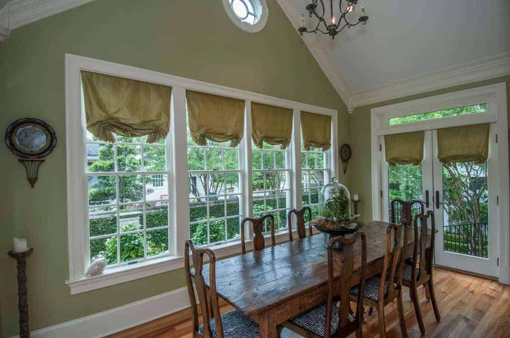 Airy dining room with cushioned chairs and a rustic dining table topped with a lovely centerpiece. It has wood plank flooring and white framed windows and double door dressed in green roman shades.