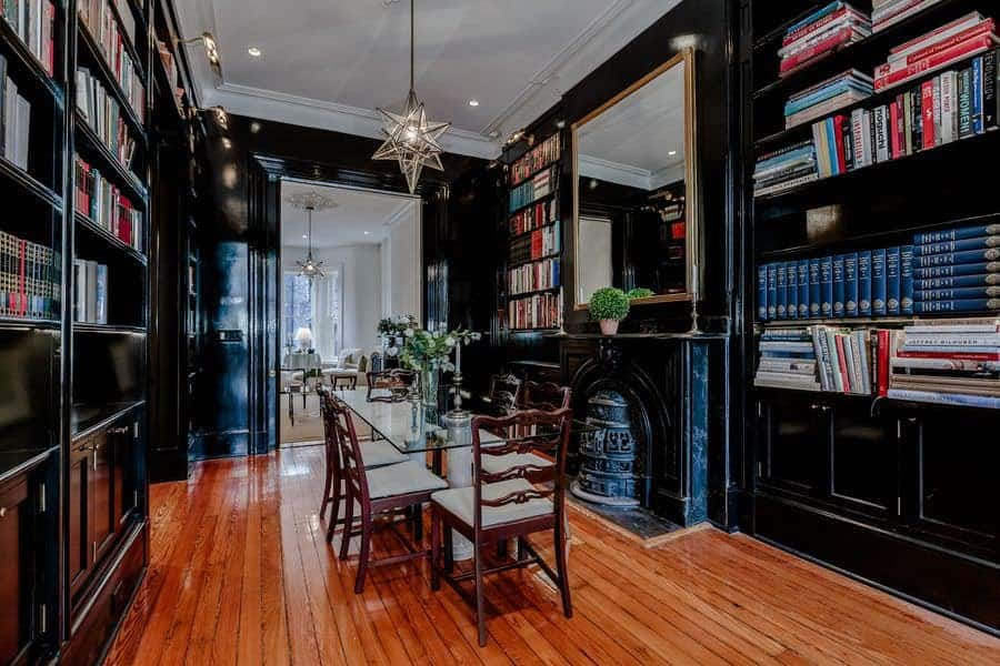 Black dining room features a glass top dining table and cushioned chairs surrounded by built-in bookshelves and brass framed mirror. It is illuminated by a star pendant along with wall sconces and recessed ceiling lights.