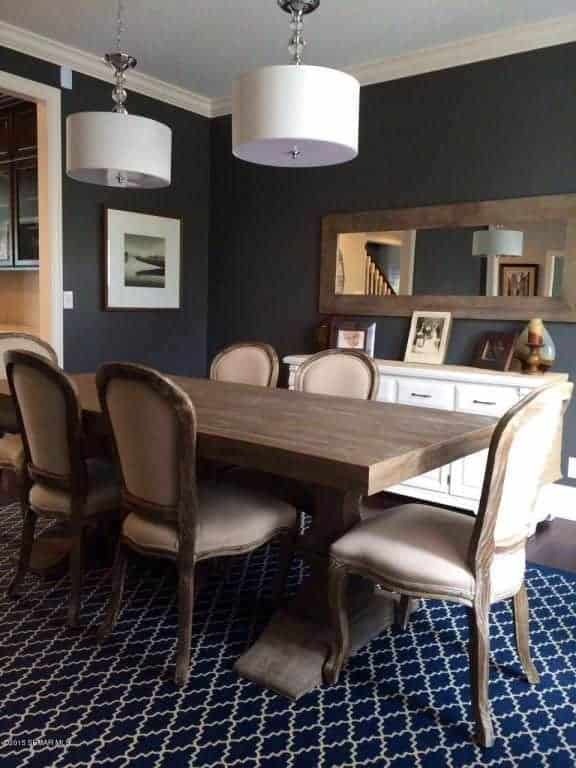 Black dining room contrasted with a pair of drum pendants and white buffet table topped with framed photos. It has a rectangular mirror complementing with the wooden dining set on an eye-catching blue patterned rug.