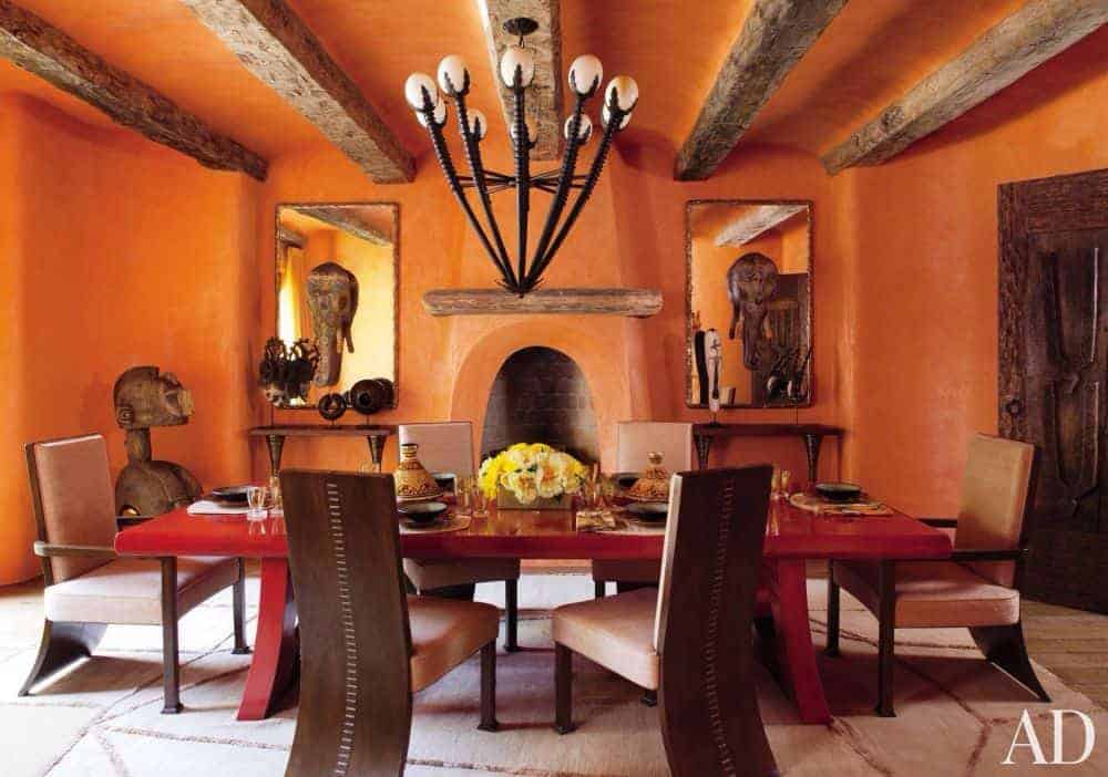 Southwestern dining room showcases upholstered chairs and a red dining table lighted by an eccentric chandelier that hung from the wood beam ceiling. It includes a beige rug and kiva fireplace flanked by mirrors and wooden shelves.