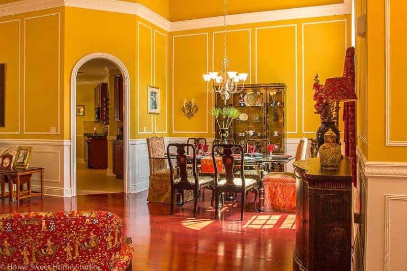 A fancy gold display cabinet faces the glass top dining table and cushioned chairs in this yellow dining area clad in full height wainscoting.