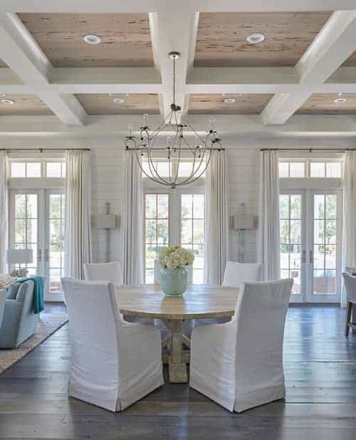 Light and airy dining room with white skirted chairs and a wooden dining table lighted by a chandelier. It has a coffered ceiling and French doors covered in white draperies.