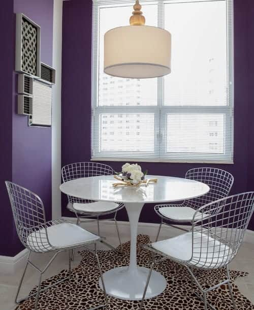 The purple dining room features a drum pendant light and white dining table paired with perforated chairs that sit on a leopard area rug.