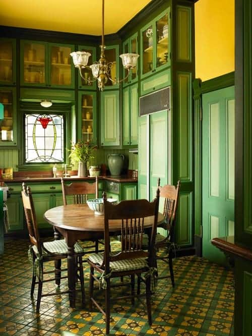 A small dining space with wooden dining table and chairs fitted with checkered cushions. It includes a brass chandelier and a stained glass window surrounded by green wainscoted and glass front cabinetry.