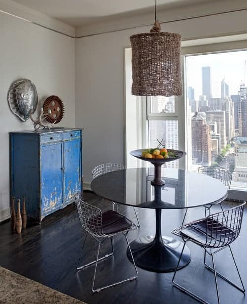 A distressed blue cabinet stands out in this dining room with dark hardwood flooring and full height windows framing an incredible city view. It has wicker pendant light and a black dining table paired with perforated chairs.