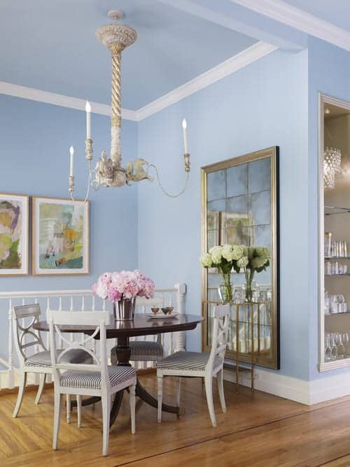 The charming dining room showcases lovely artworks and a paneled mirror mounted on the sky blue wall. It has a candle chandelier and striped cushioned chairs surrounding a dark wood dining table.