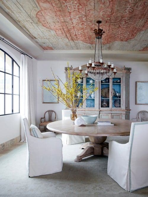 Shabby-chic style dining room offers a wooden dining table complementing with the china cabinet and wide plank tray ceiling designed with a red print. It includes a crystal chandelier and white skirted chairs that sit on a vintage rug.
