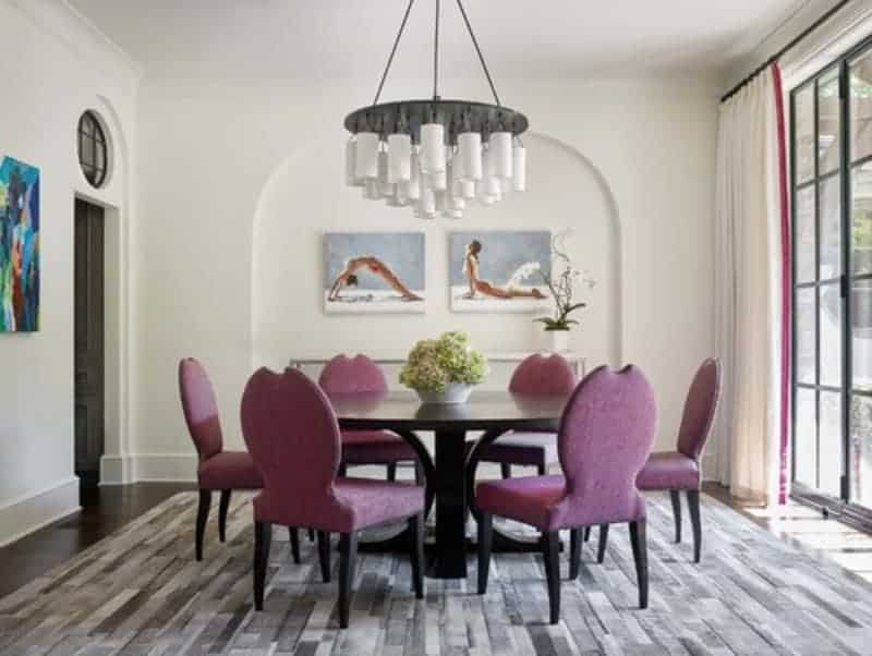 Stylish plum round back chairs on a striking area rug add a nice accent in this white dining room featuring a round chandelier and lovely canvases mounted on the arched inset wall.