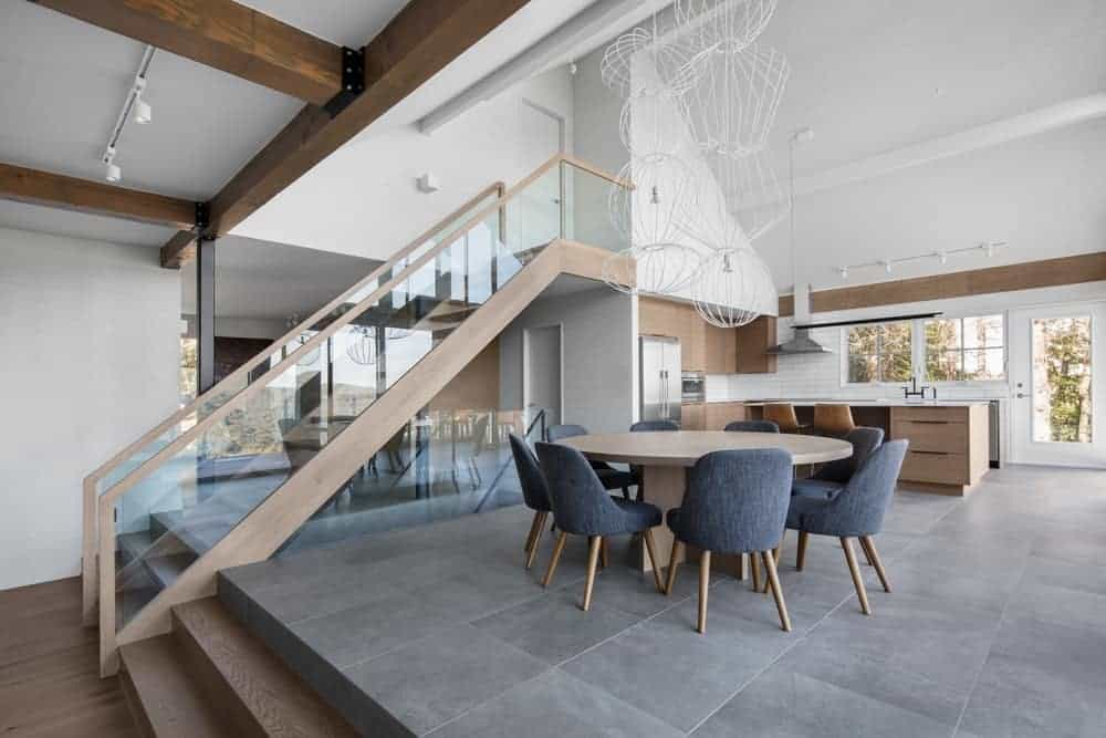An open dining area features gray modern chairs and a light wood dining table illuminated by white industrial pendants. It is situated beside the staircase sharing space with the kitchen.
