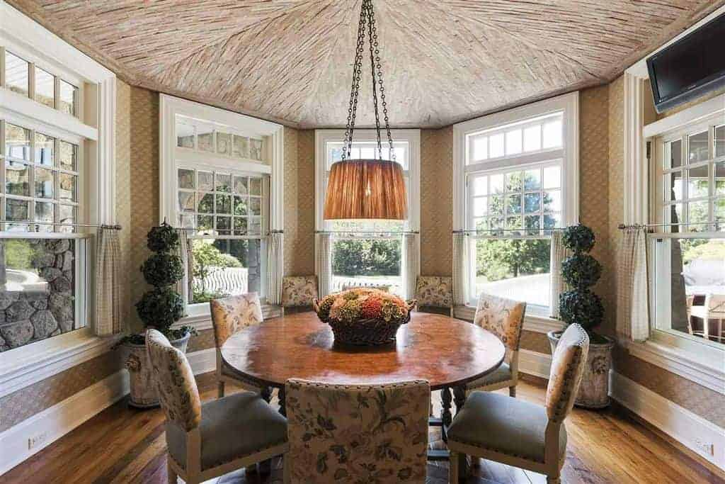 A warm pendant light hangs over the round wooden table in this dining room showcasing floral cushioned chairs and white framed windows inviting natural light in.