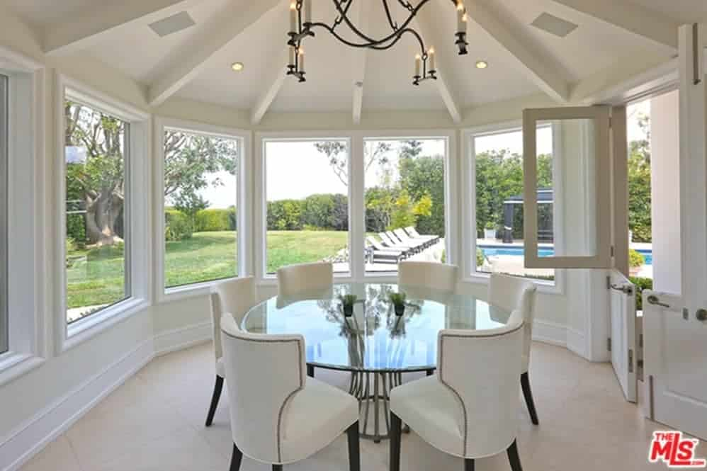 White dining room with beamed ceiling and glass paneled windows overlooking the lush green outdoor with a sparkling pool. It has a candle chandelier and a glass top dining table paired with white wingback chairs.