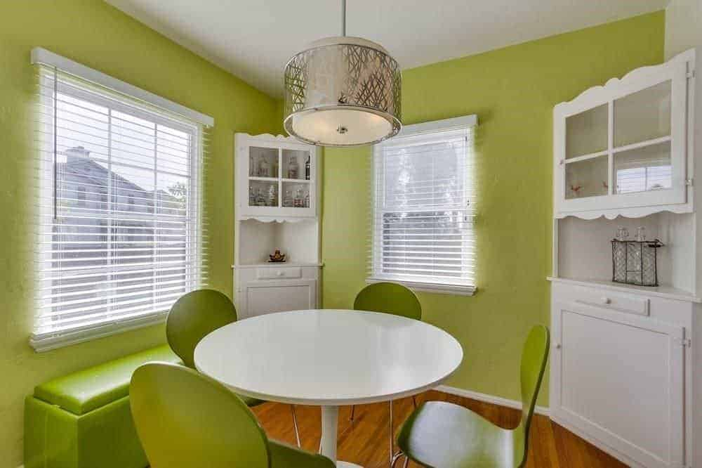 A stylish drum pendant illuminates this green dining room featuring a round dining set accompanied by a built-in bench and white corner cabinets.