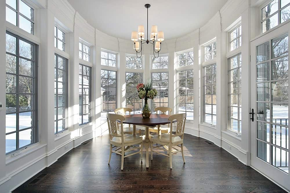 Ample natural light flows in through the framed windows in this serene dining room showcasing a shade chandelier and a round dining table paired with wooden chairs.